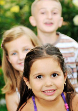 Photo of three kids, one standing behind another. First is a dark-haired girl, followed by a blonde girl, and a blonde boy; for information on Chatham NJ pediatric dentistry.